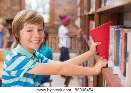 Cute pupil looking for books in library at the elementary school