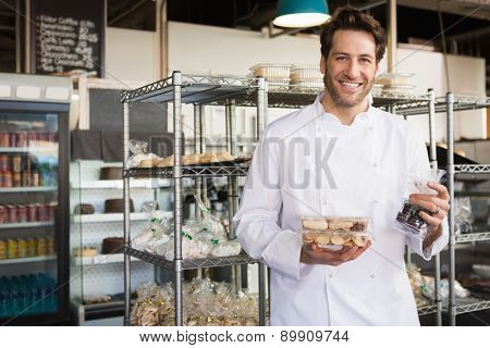 Cheerful baker holding coffee house and food at the bakery