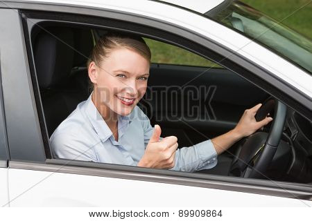 Smiling businesswoman sitting in drivers seat in her car