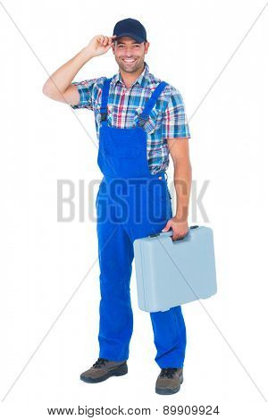 Portrait of happy manual worker wearing cap while carrying toolbox on white background