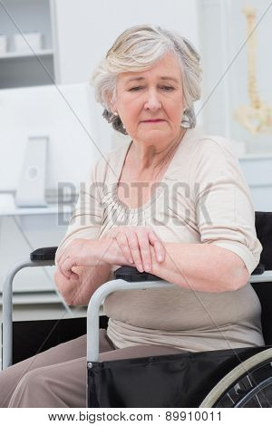 Thoughtful sad senior patient sitting in wheelchair at clinic