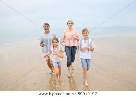 Happy family of four running on a sandy beach