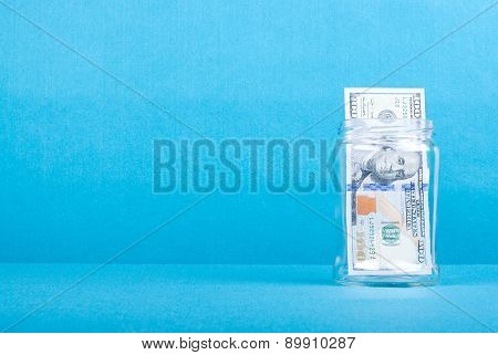 One Hundred Dollars In A Glass Jar On The Right Side, Side View, Place For Text