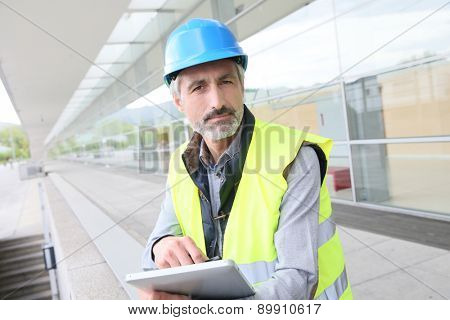 Engineer with hard hat using tablet outside building
