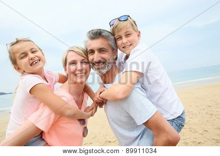 Parents giving piggyback ride to children at the beach