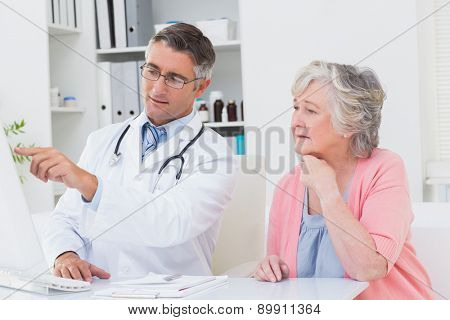 Male doctor showing reports to senior patient on computer in clinic