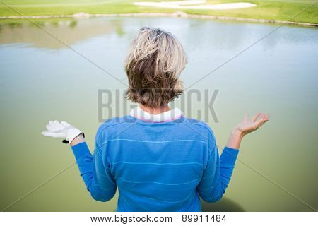 Confused female golfer looking at lake on a sunny day at the golf course