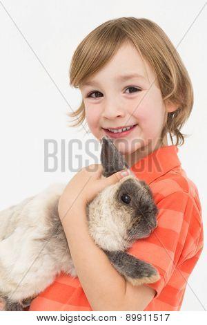 Portrait of happy boy holding fluffy rabbit on white background