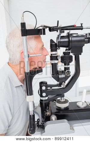 Senior male patient looking into slit lamp at clinic