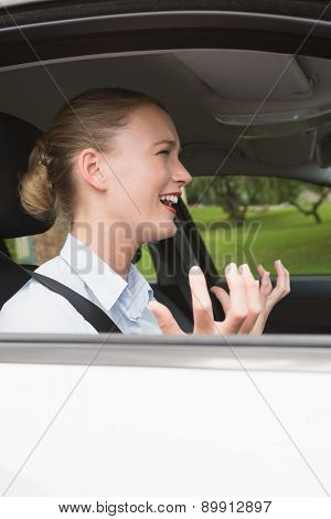 Young businesswoman experiencing road rage in her car