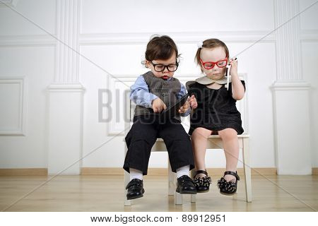 Two little child sitting on white chairs: boy in black glasses with tablet computer and girl in red glasses talking on the mobile phone