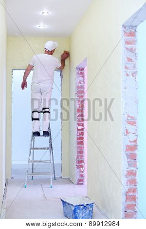 Builder polishing the wall in the corner with a cleaning sponge