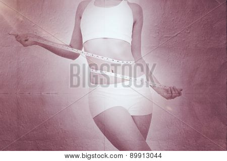 Slim woman measuring waist with tape measure against grey concrete tile