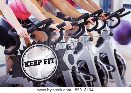 The word keep fit and mid section of people working out at spinning class against badge