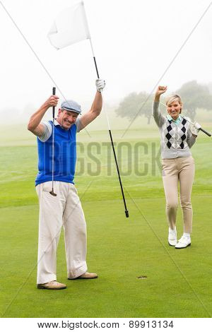 Golfing couple cheering on the putting green on a foggy day at the golf course