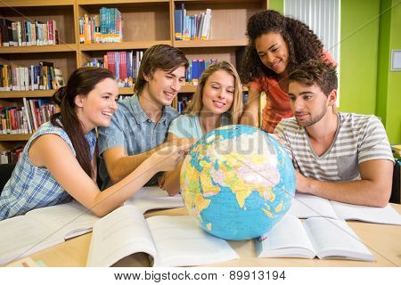 Group of college students pointing at globe in the library