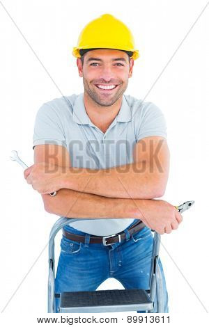 Portrait of handyman with hand tools on step ladder over white background