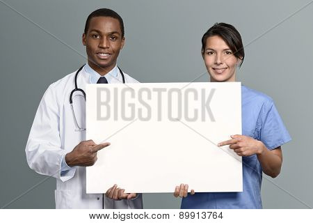Multiethnic Medical Team Holding A White Sign