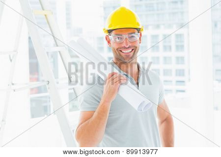 Portrait of smiling handyman holding rolled up blueprint in bright office