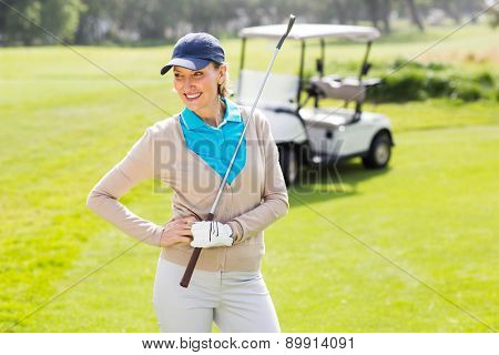 Female golfer smiling with hands on hip on a sunny day at the golf course