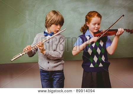 Portrait of cute little students playing flute and violin in classroom
