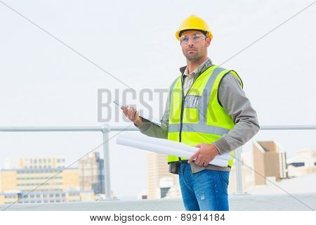 Male architect in protective clothing holding blueprints and clipboard outdoors