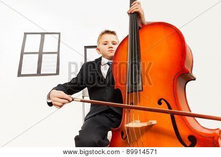 Boy playing violoncello sitting on the chair