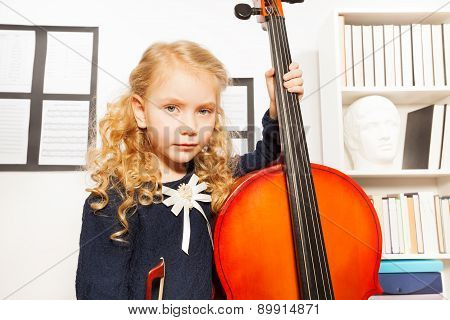 Blond girl with curly hair holds cello to play