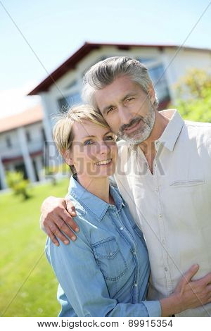 Couple standing in front of newly owned house