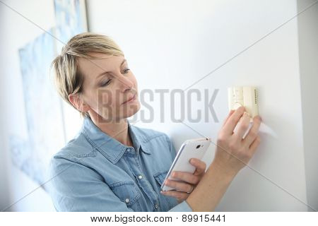 Woman porgramming indoor temperature with smartphone application