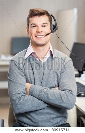 Portrait of confident male customer service representative with arms crossed sitting in office