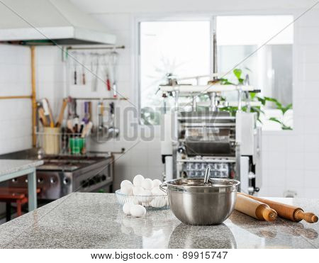 Mixing bowl with eggs and rolling pin on counter in commercial kitchen