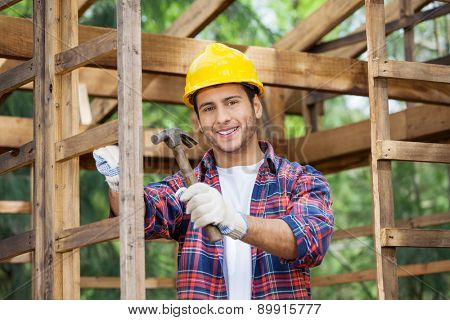 Portrait of happy male construction worker holding hammer in incomplete wooden cabin at site