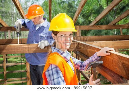 Portrait of smiling female worker holding hammer while colleague working in background at construction site
