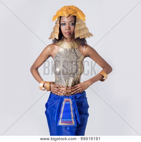 elegant beautiful dark-skinned woman in a suit of the Egyptian queen Cleopatra in gold tones
