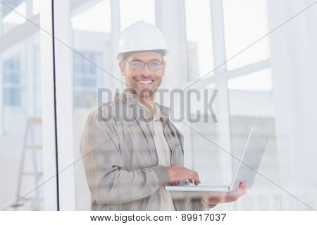 Portrait of smiling male architect using laptop in office