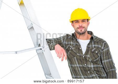 Smiling handyman in overalls leaning on ladder at bright office