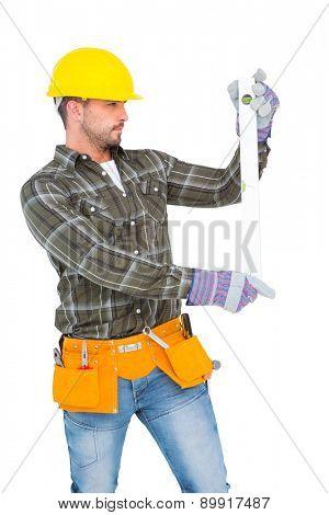 Serious handyman using spirit level on white background