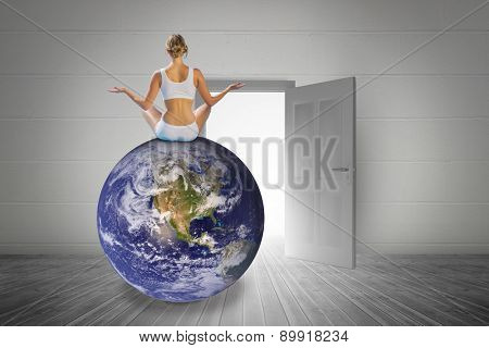 Fit woman doing yoga against open door on white wall