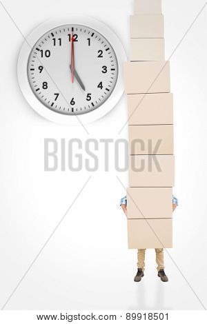 Man carrying pile of boxes against five o clock