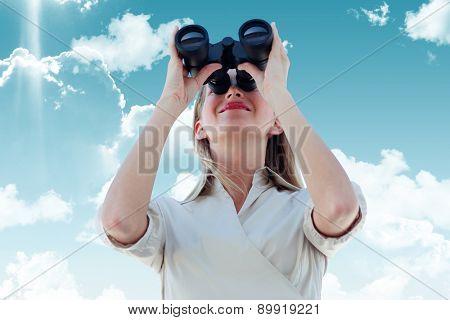 Businesswoman looking through binoculars against blue sky