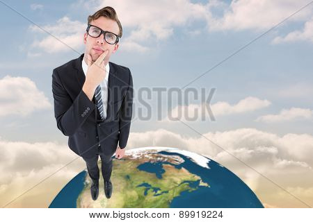 Thoughtful geeky hipster businessman looking up against beautiful blue sky with clouds