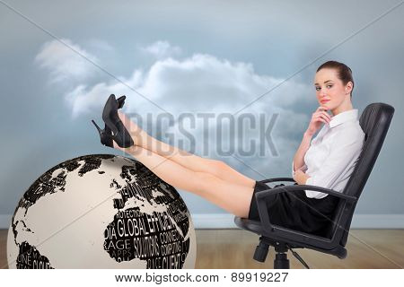 Businesswoman sitting on swivel chair with feet up against clouds in a room