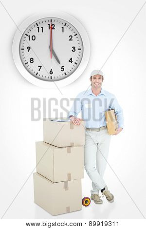 Handsome delivery man leaning on stacked cardboard boxes against five o clock