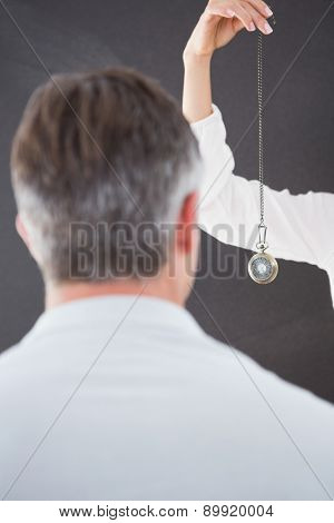 Man being hypnotized with pendulum