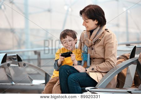 Loving mother and son using smartphone