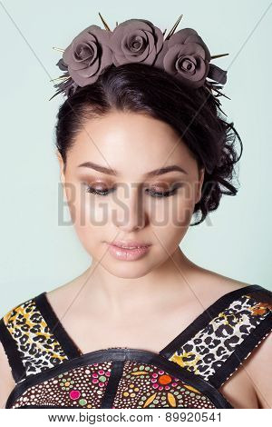 portrait of a girl brunete with hair beam with a delicate make up and a wreath in her hair from blac