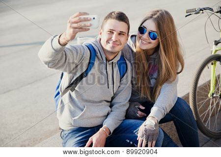 young couple using smart phone for selfie in the city