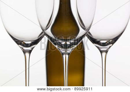 Three Empty Glasses Of Wine And Brown Bottle