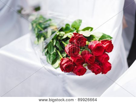 Bouquet Of Red Roses Laying At The Banquet Chair